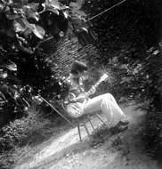 Hugh plays guitar in the small yard that was the back garden.