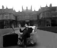 Hugh (again in frog mask) relaxes in chair in the Corsham court driveway.